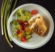 breaded codfish plated with vegetables cucumber tomatoes